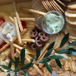 A large box containing crackers, cheeses and dips