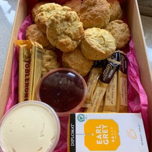 A box containing scones, jam, cream, tea, coffee and chocolate