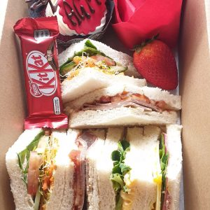 Box containing sandwiches, chocolate, fruit and a cake