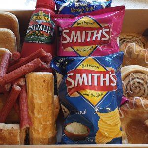 A box containing pies, sausage rolls, tomato sauce, savoury snacks, pastries and cakes